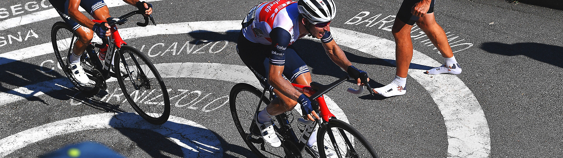 Lookdown view of Trek-Segafredo riders climbing a road with names painted in pavement.